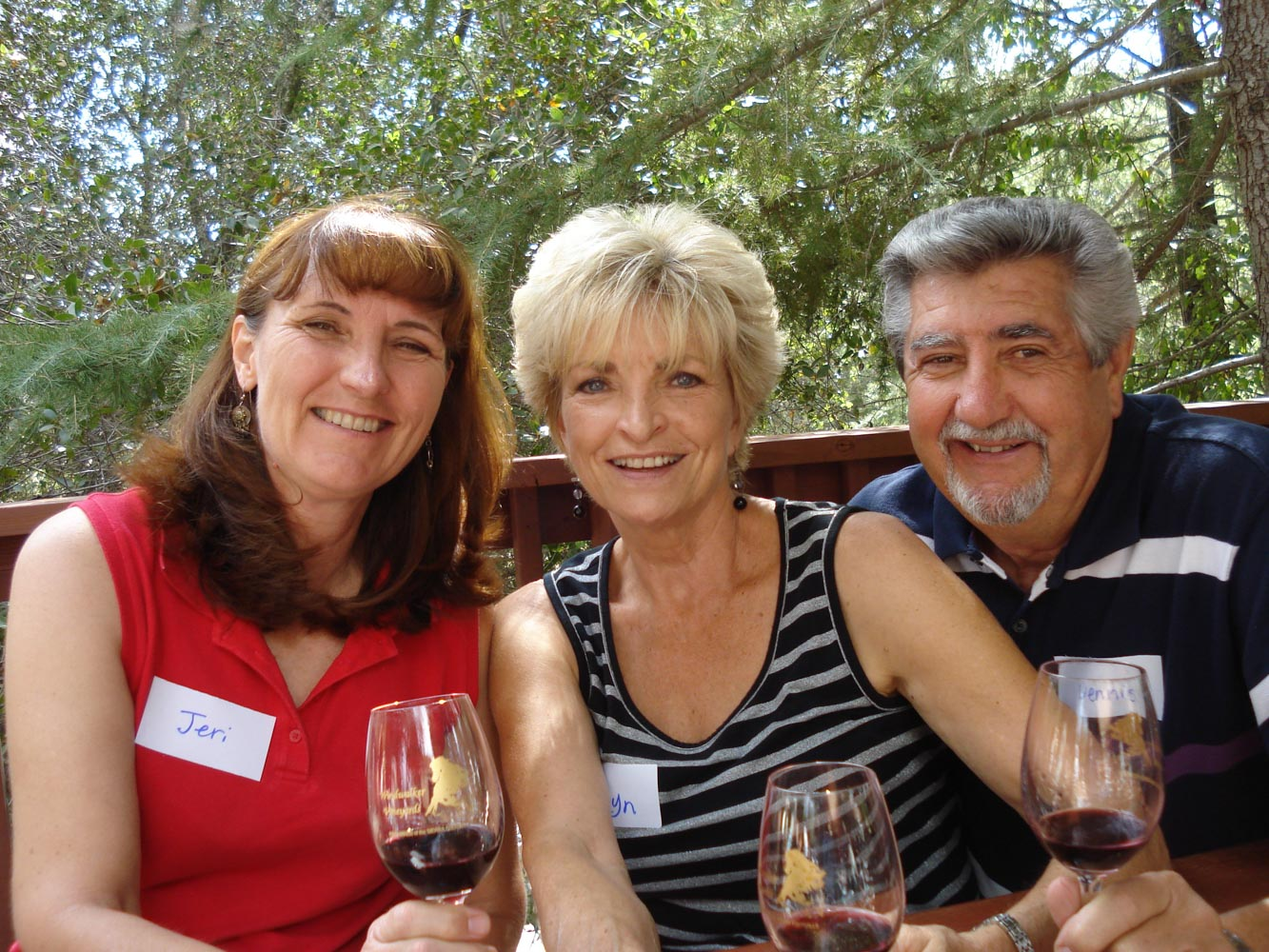Close-up portrait of two women and one man, all smiling and holding a glass of red wine.