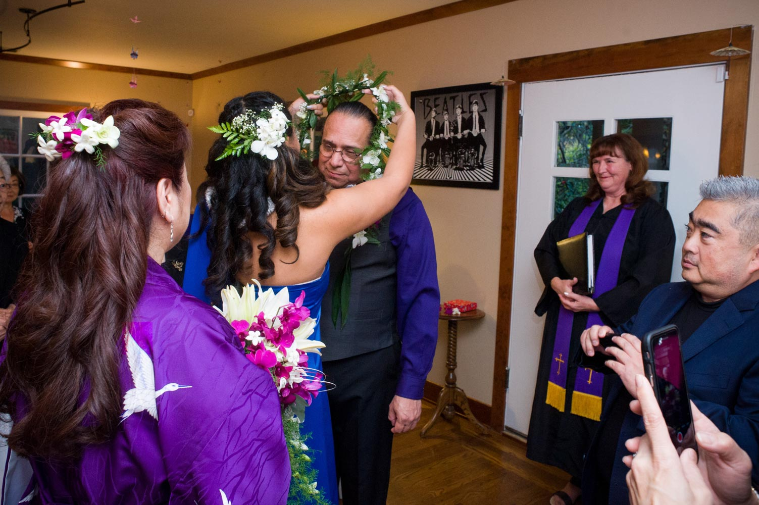 Girl places lei on groom, while wedding officiant watchs