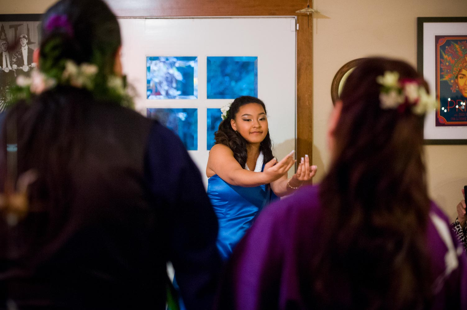 Girl, facing forward, performs hula dance as seen from behind observing couple