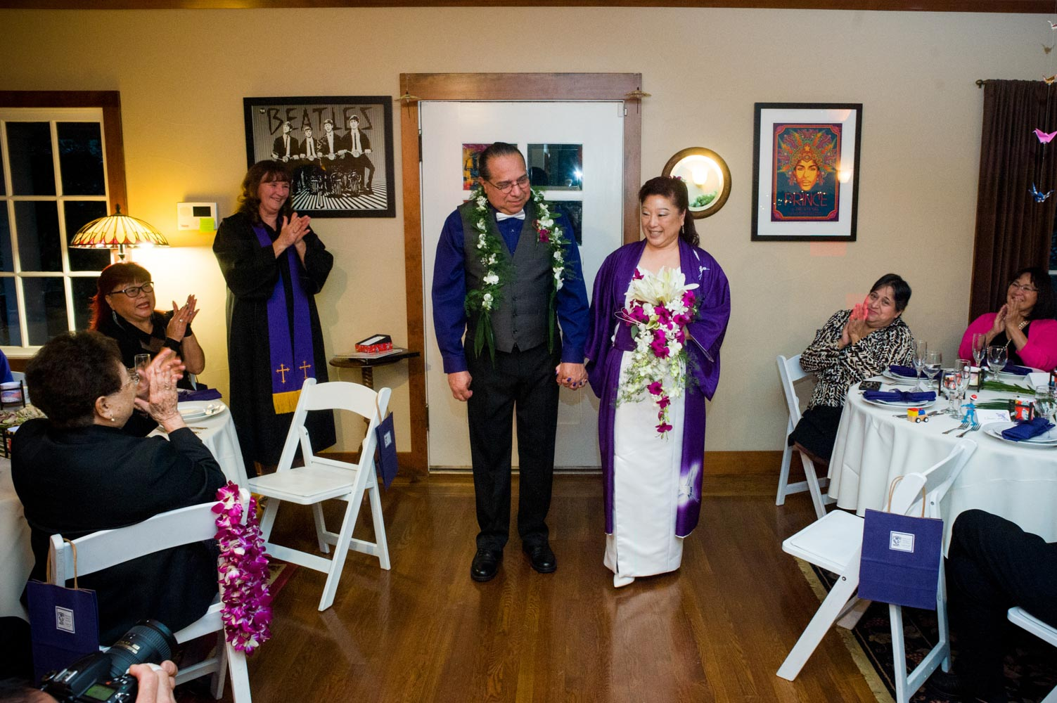 Bride and groom smiling at guests, which wedding officiant applauds in background.