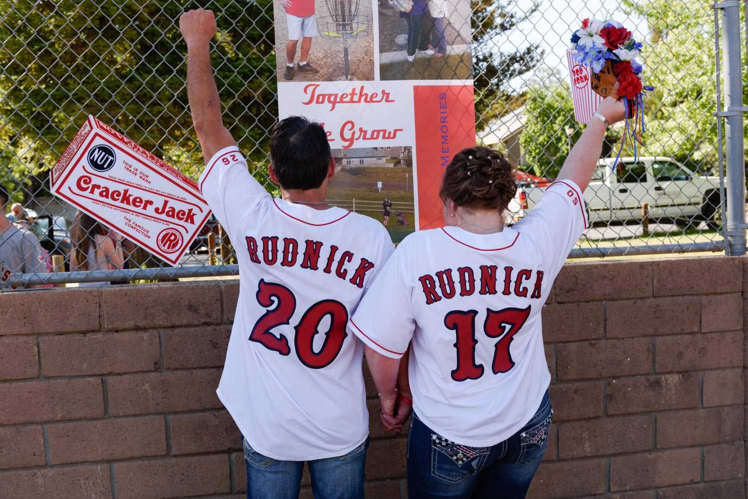Back view of man and woman wearing white baseball jerseys, with arms raised in celebration after their wedding ceremony.