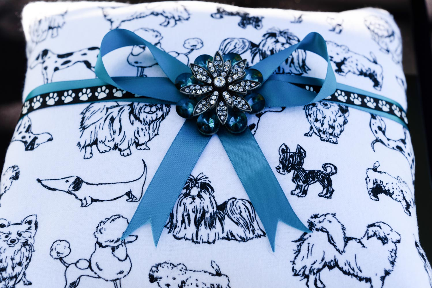 White ring bearer's pillow, with black drwings of dogs, tied with blue ribbon.