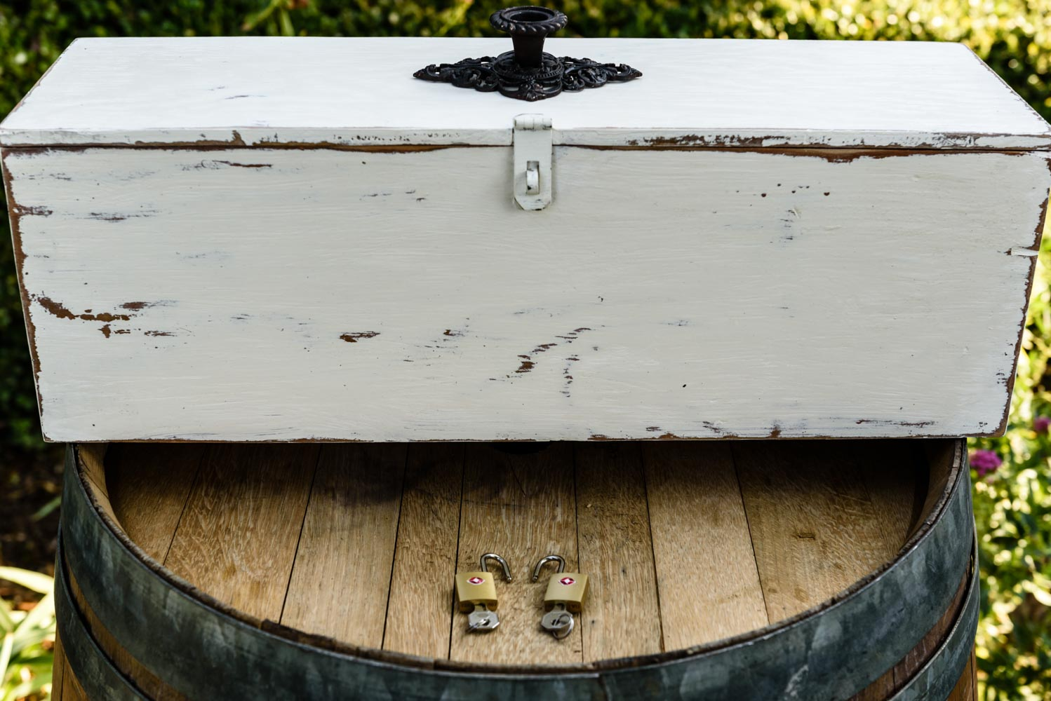 White lockable box, sitting on top of wine barrel, with two locks and keys placed nearby