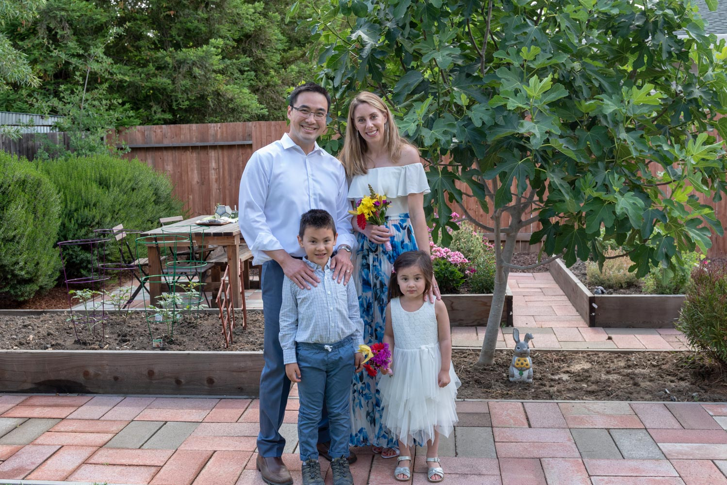 Father, mother and two children standing on patio near garden