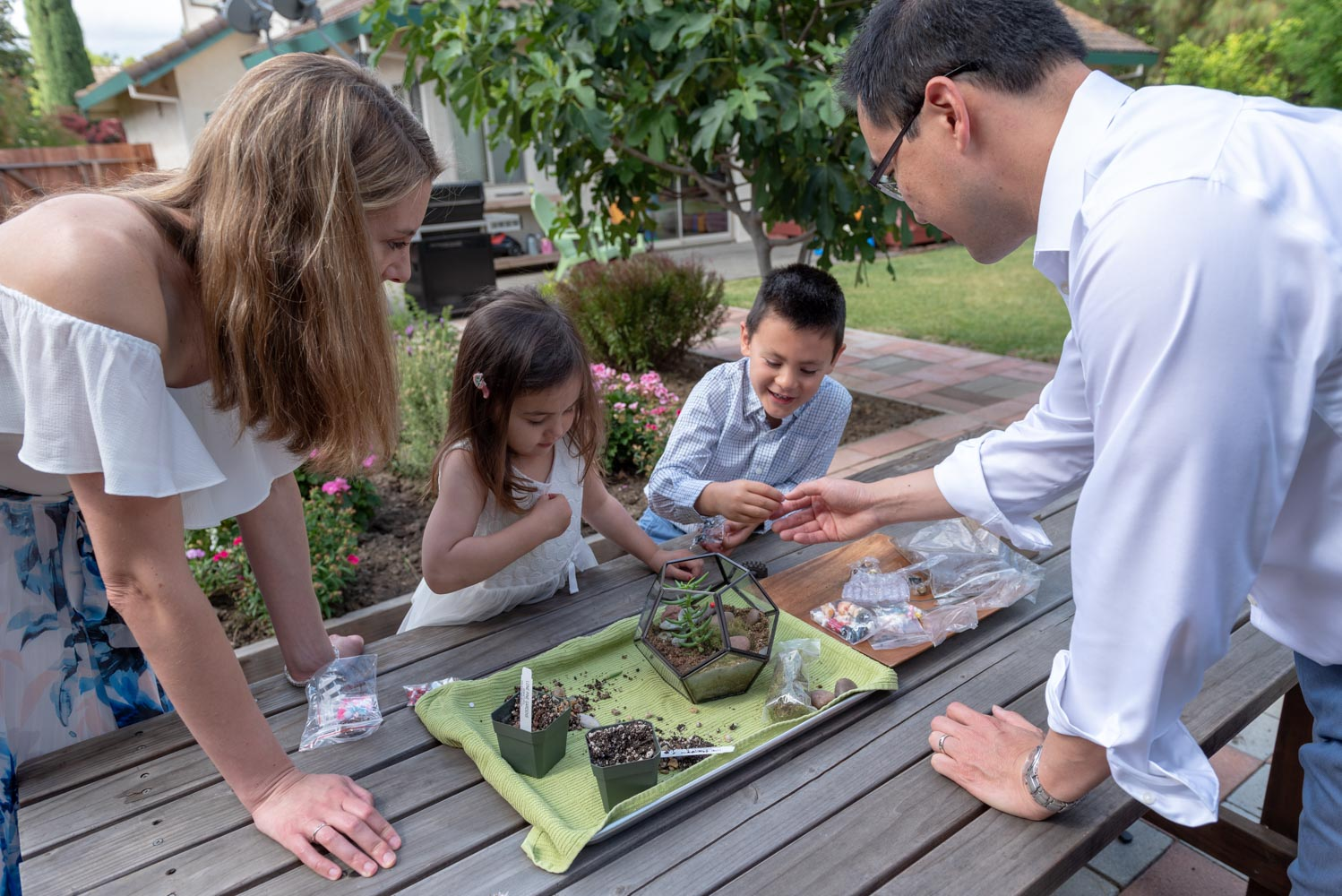Parents and two young children planting a terrarium.