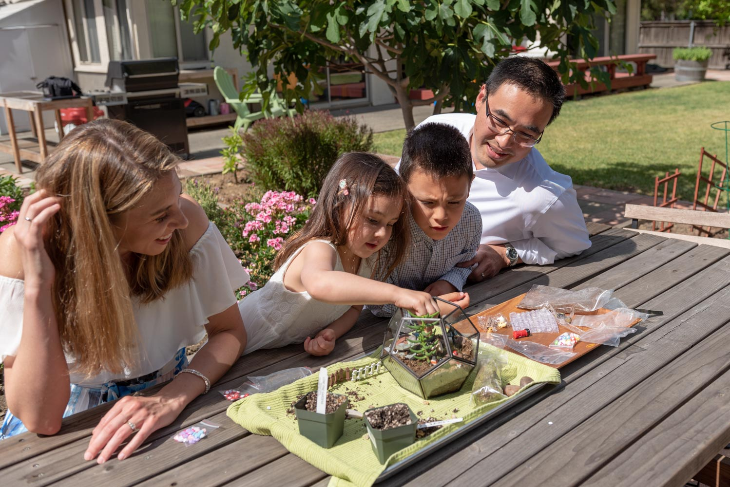 Parents and children sitting on picnic bench and planting terrarium.