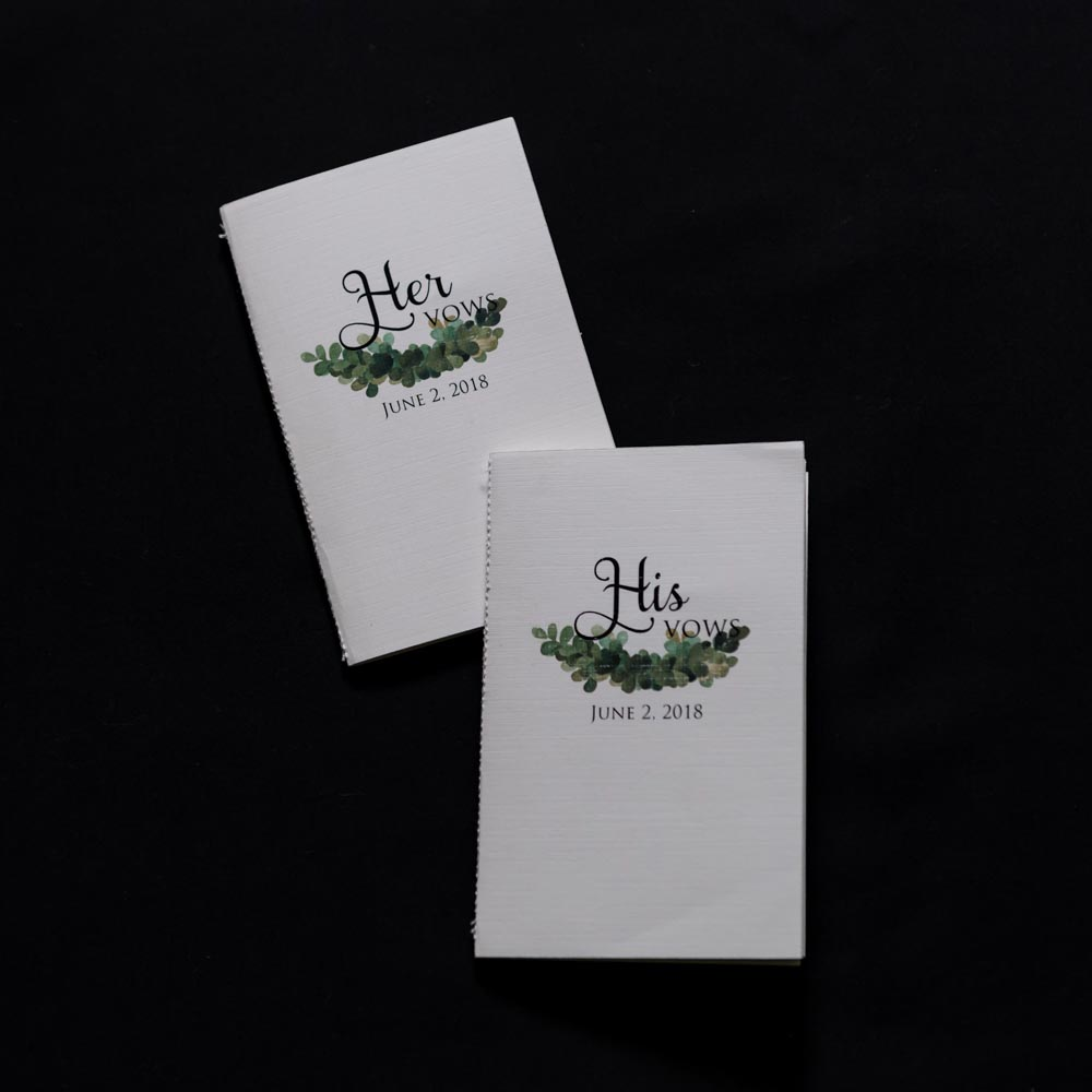 Two white vow booklets on black background