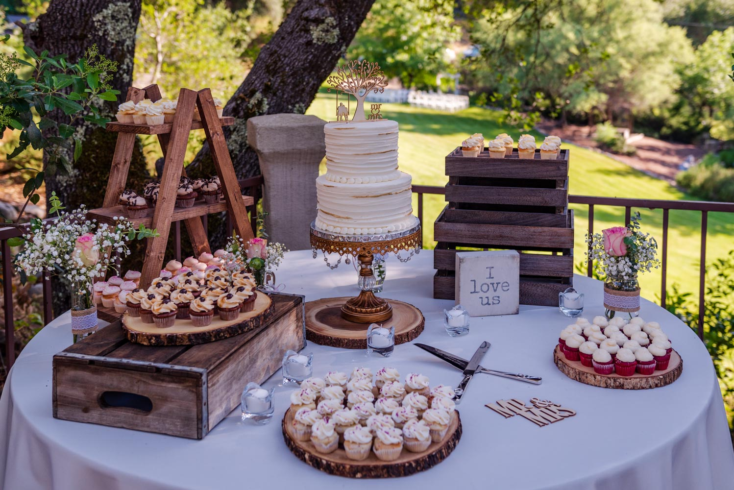 Linen-covered table with wedding cake and desserts