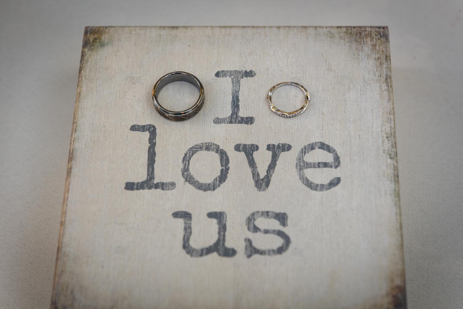 """I love us"" sign with wedding rings"