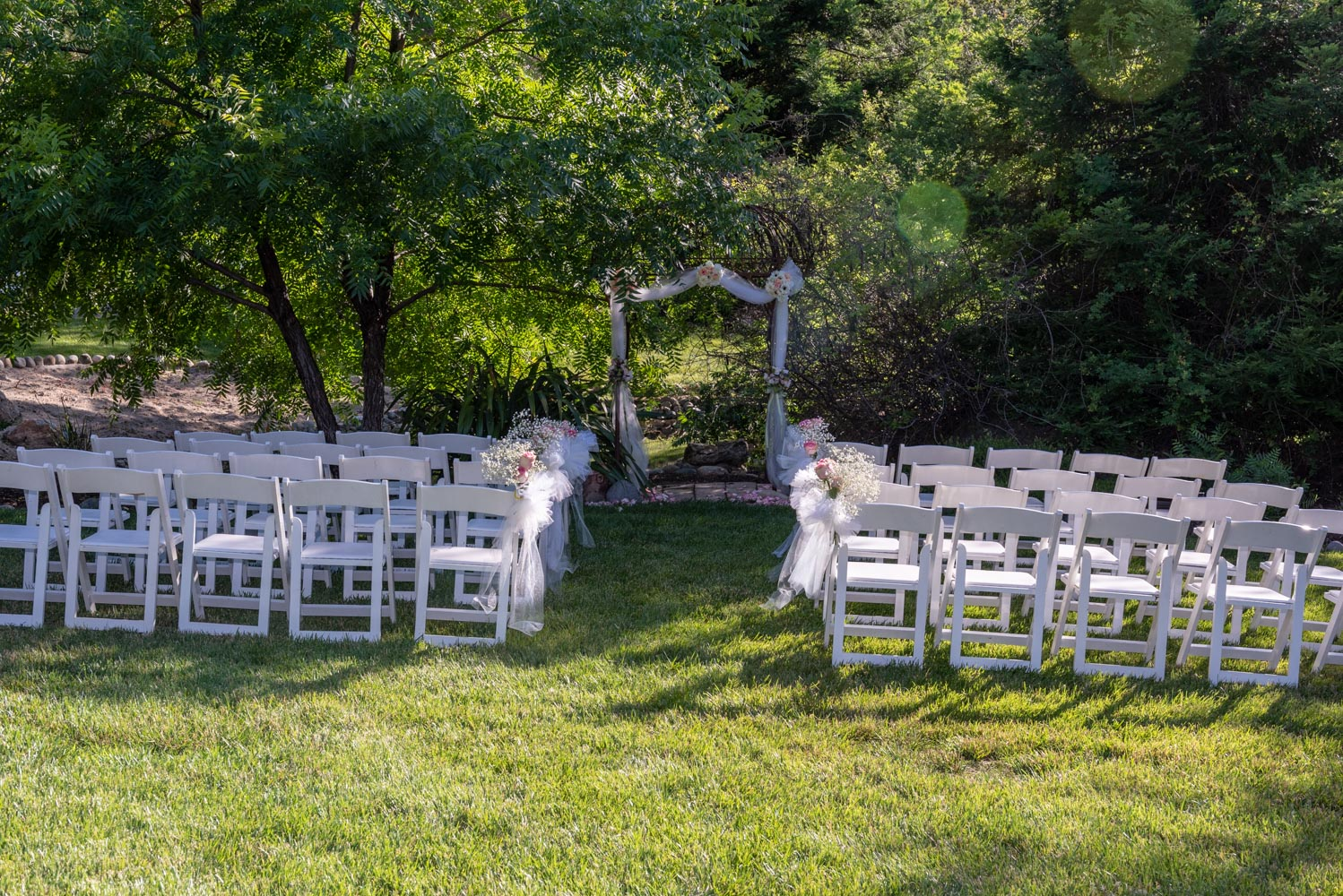 Garden ceremony site, with white chairs and decorated wedding arch