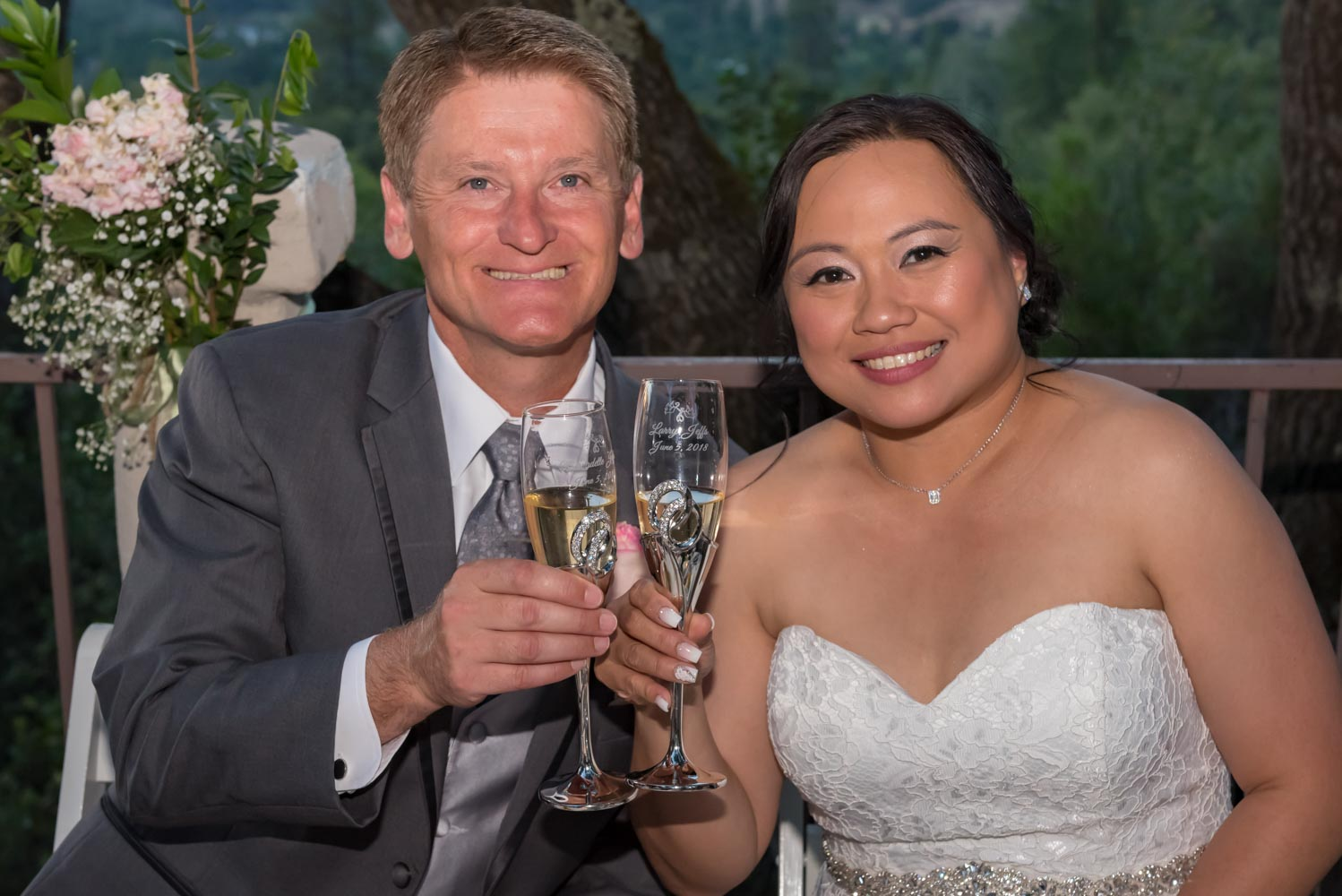 Portrait of bride and groom smiling and holding toasting glasses