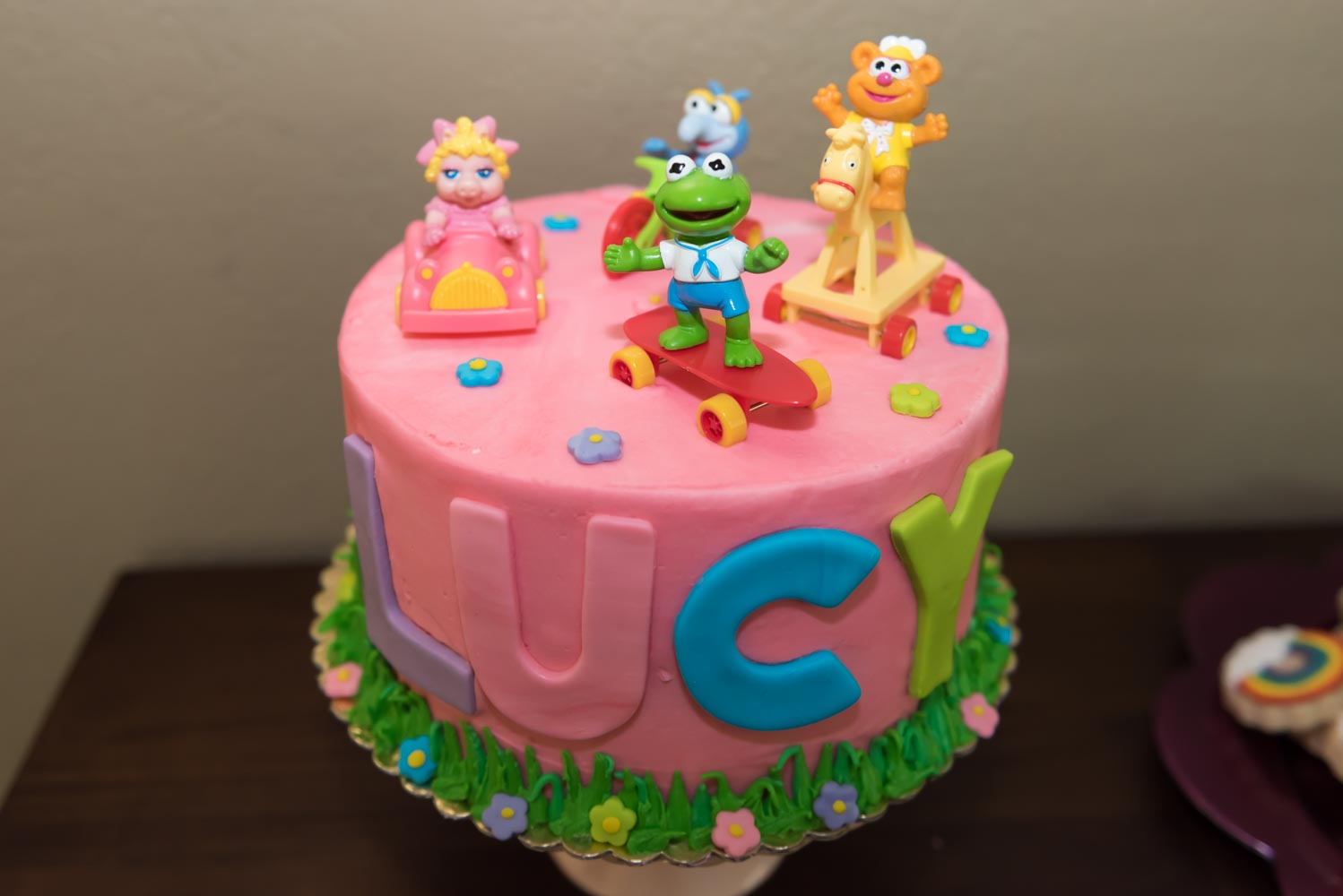 "Pink cake with Muppet Babies figurines on top and ""Lucy"" written on side."