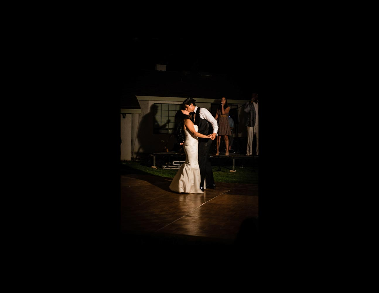 Nighttime photo of bride and groom dancing during wedding reception