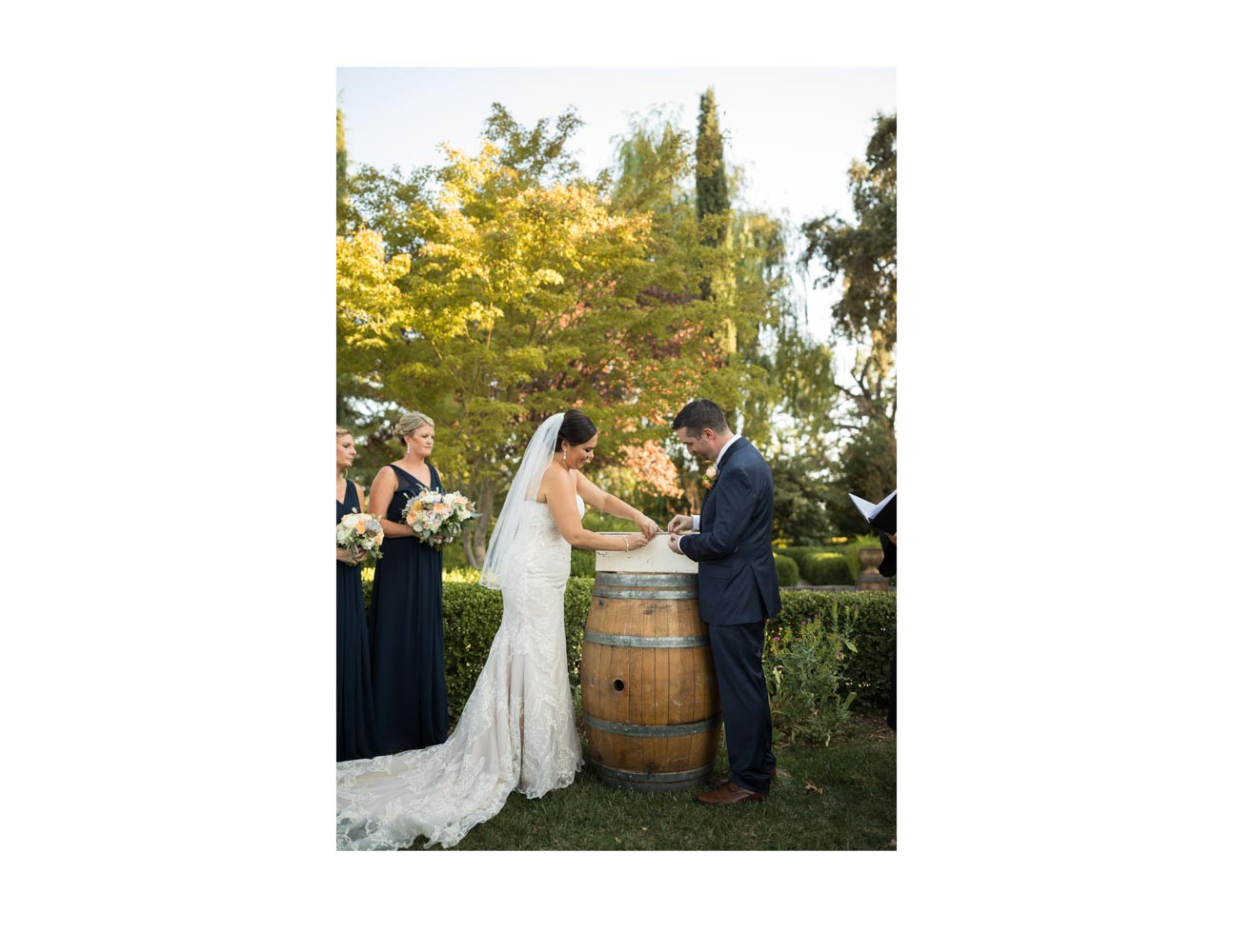 Bride and groom locking white box, which is sitting on wine barrel in garden setting