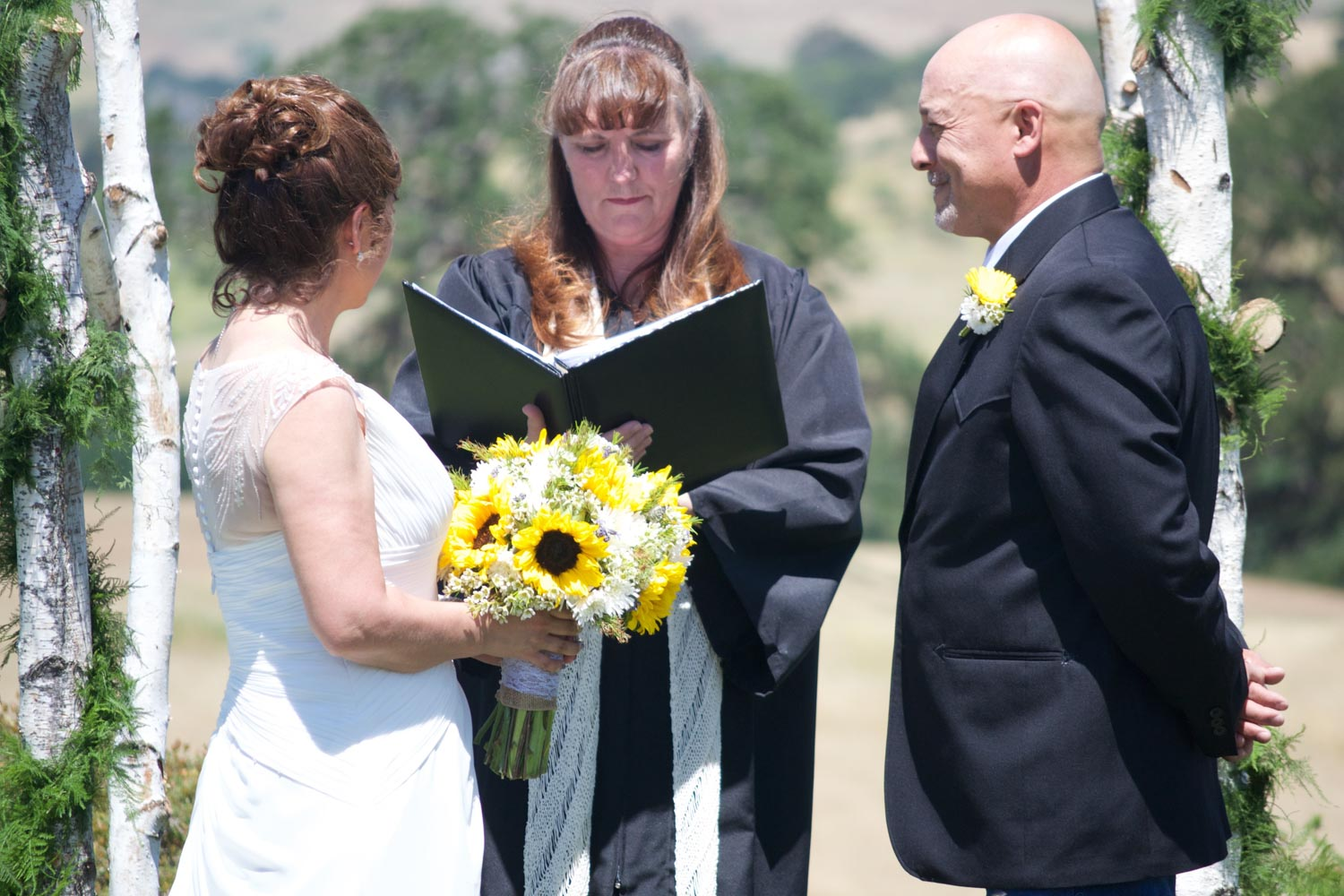 Bride and groom looking at officiant during wedding ceremony.