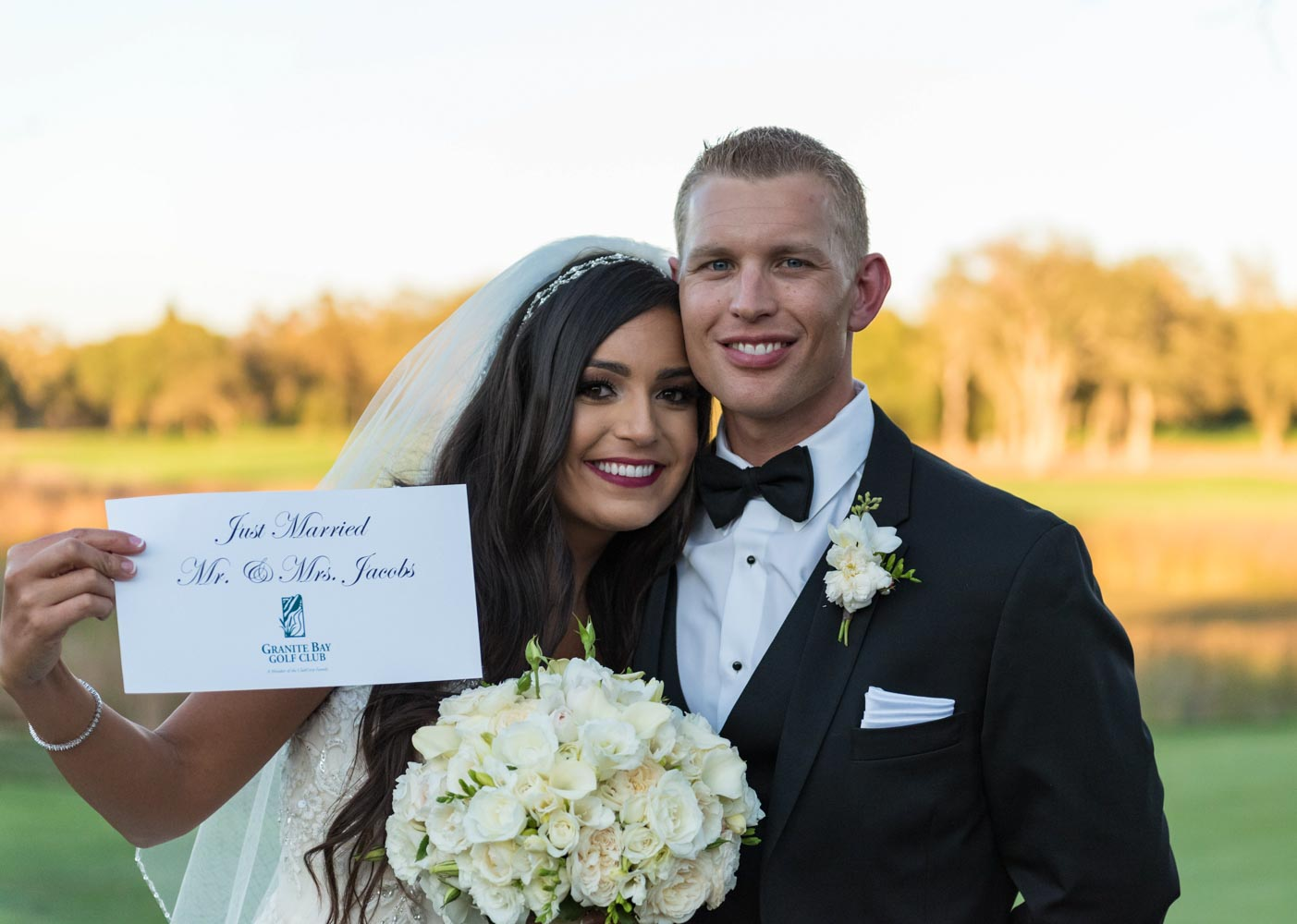 """Bride, holding bouquet and """"Just Married"""" sign, standing with groom"""
