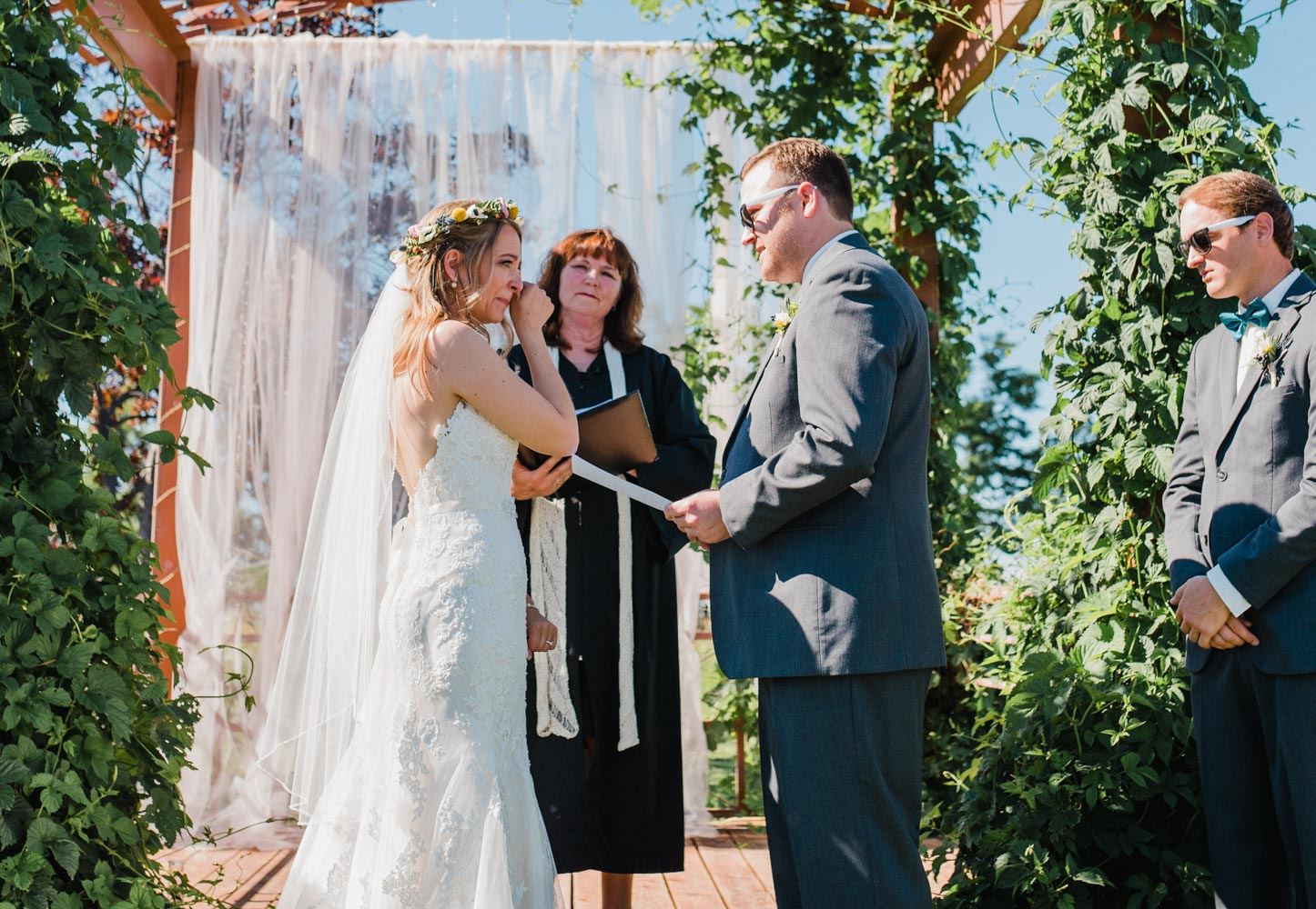 Bride wiping her tears as groom reads vows, with wedding officiant listening in background