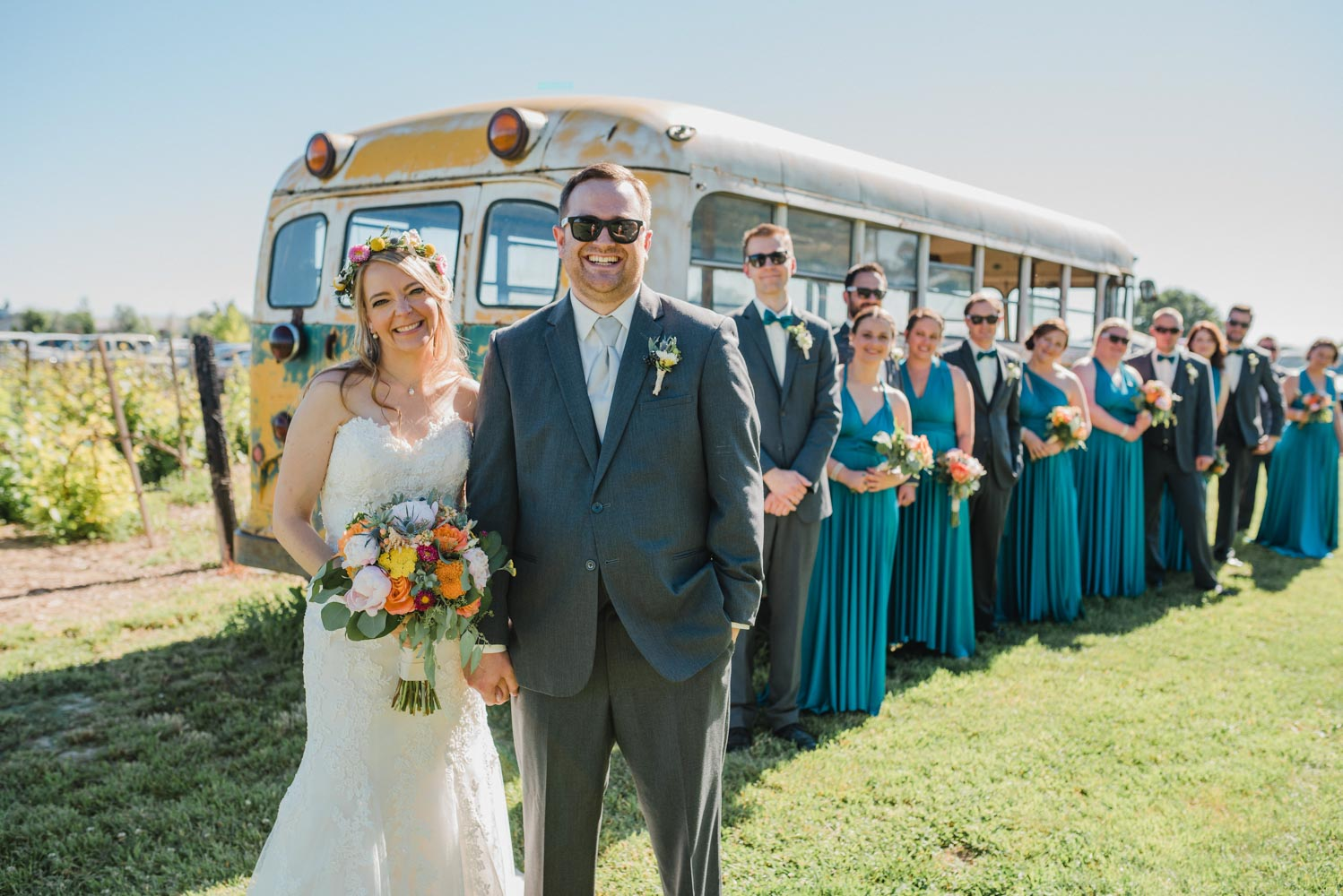 Bride and groom in foreground, with wedding party standing by yellow school bus behind them