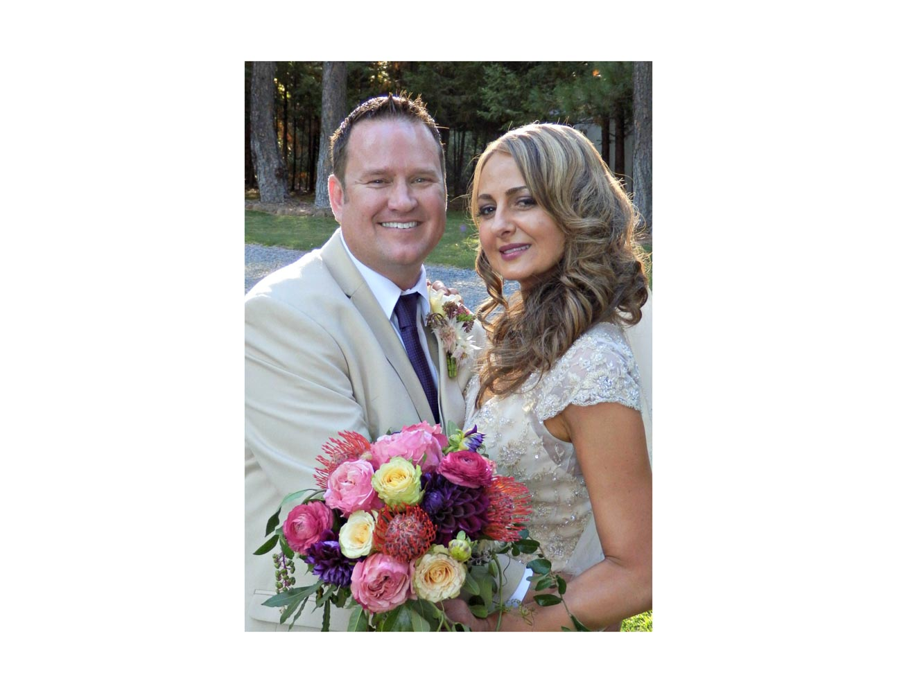 Closeup of smiling groom and bride, holding bouquet, in outdoor wedding location