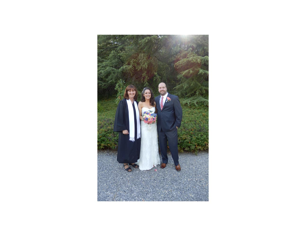 Minister, bride and groom standing on driveway of outdoor wedding venue