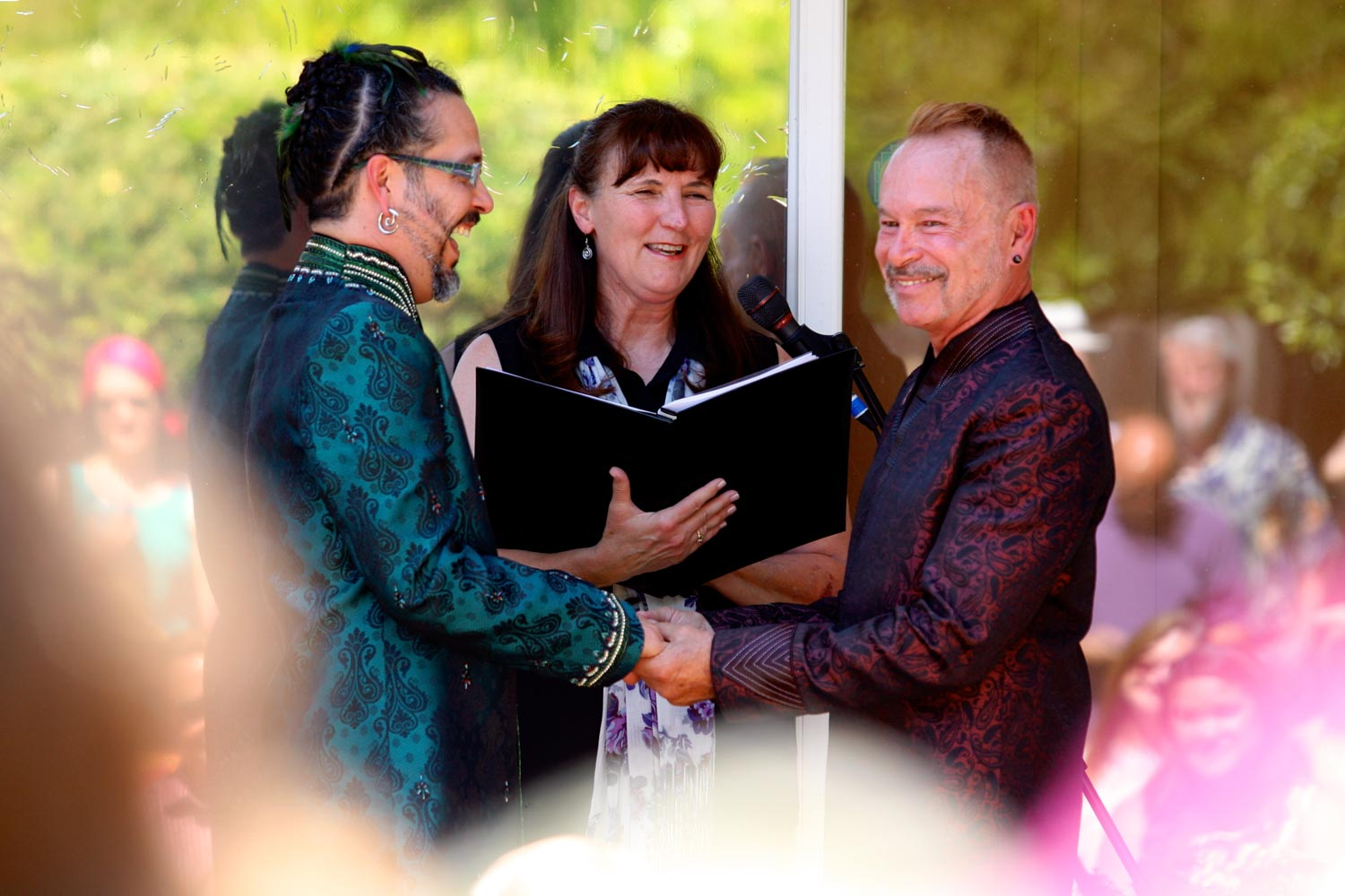 Two grooms laughing during wedding ceremony, with officiant in background
