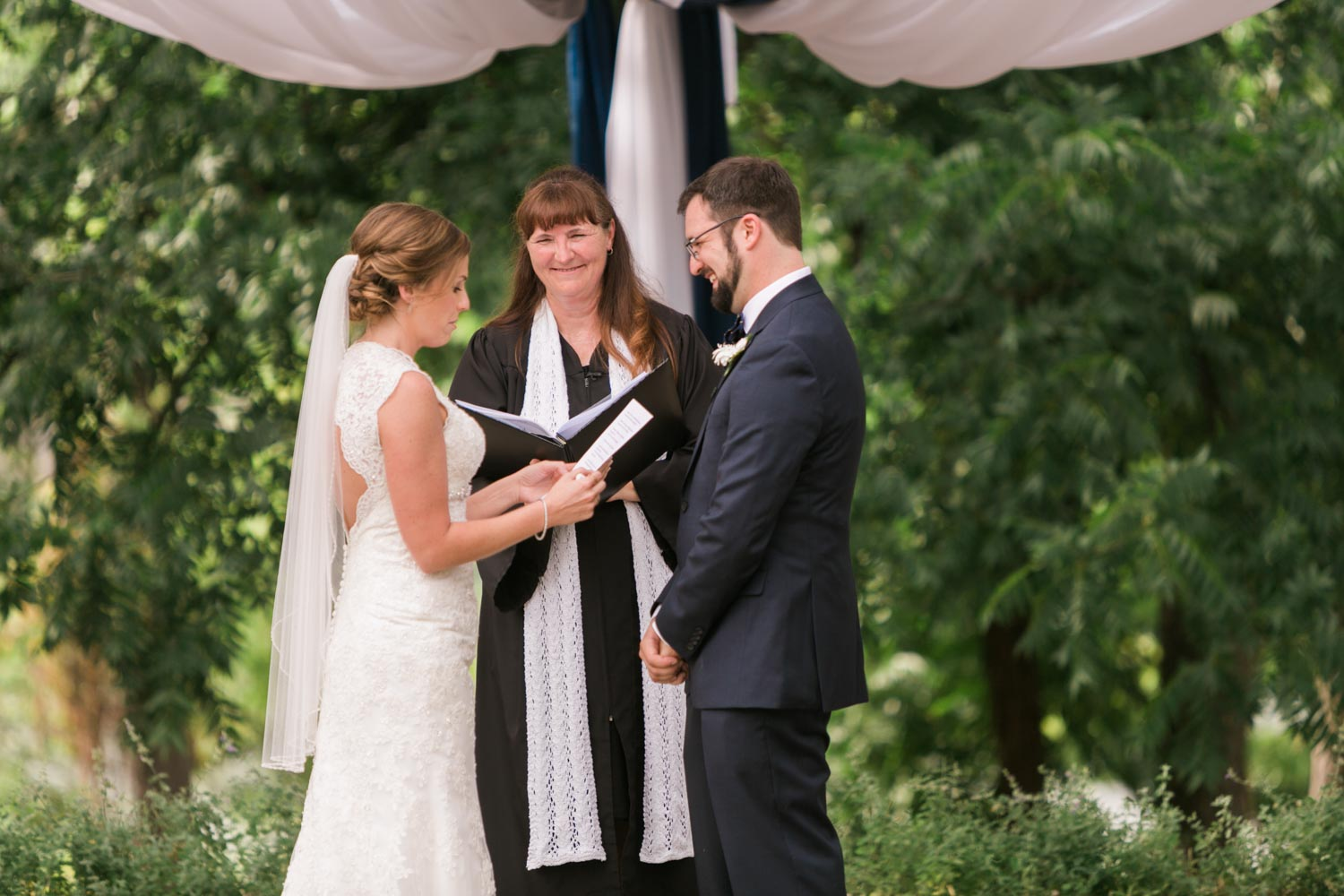 Bride reading vows to smiling groom, with wedding officiant listening in background