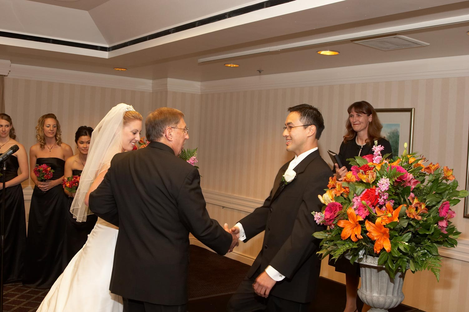 Bride and her father greeting groom at beginning of wedding ceremony