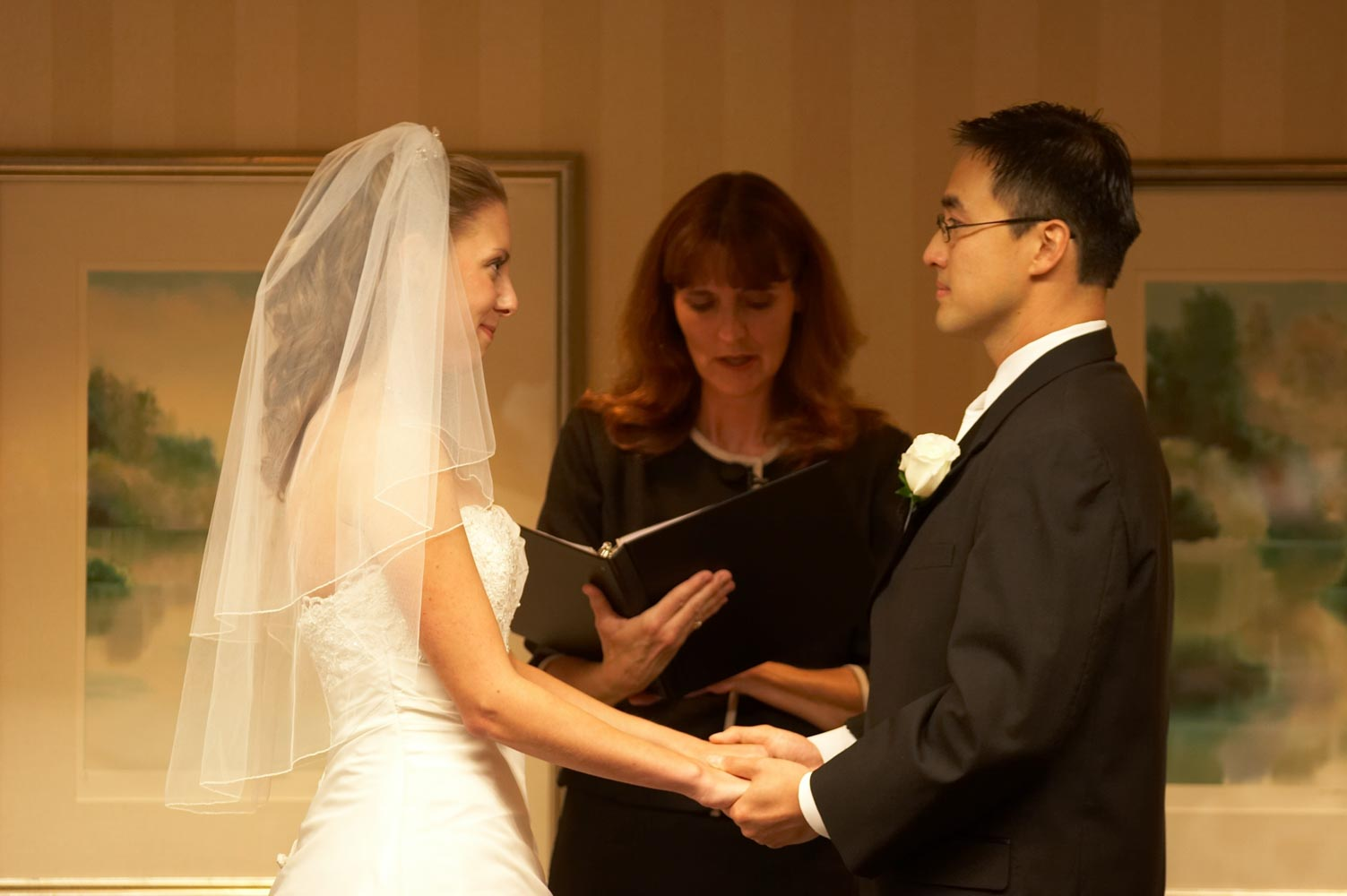 Bride and groom facing each other while minister reads wedding ceremony