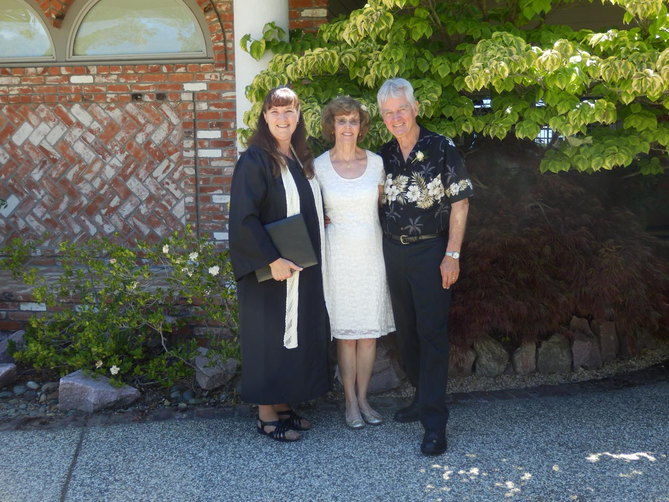 Minister, bride and groom standing near brick wall at home wedding