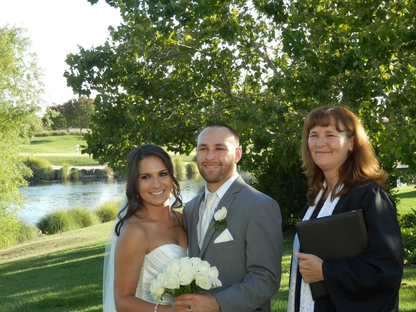 Smiling bride, groom and minister with golf course and water feature in background