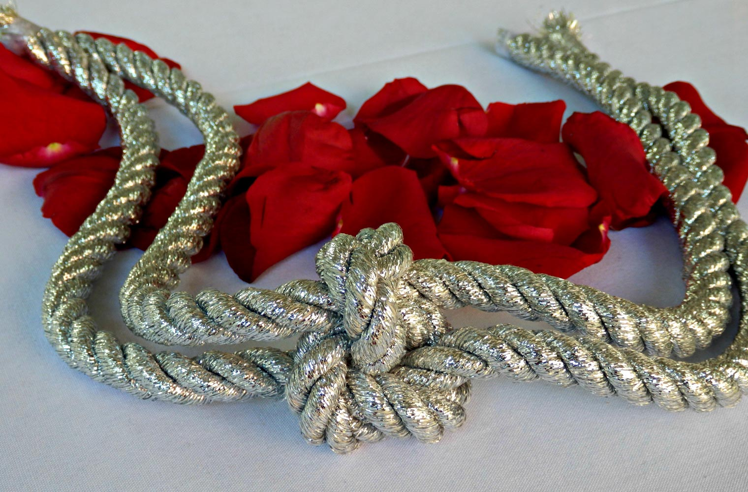 Silver lovers' knot and red rose petals