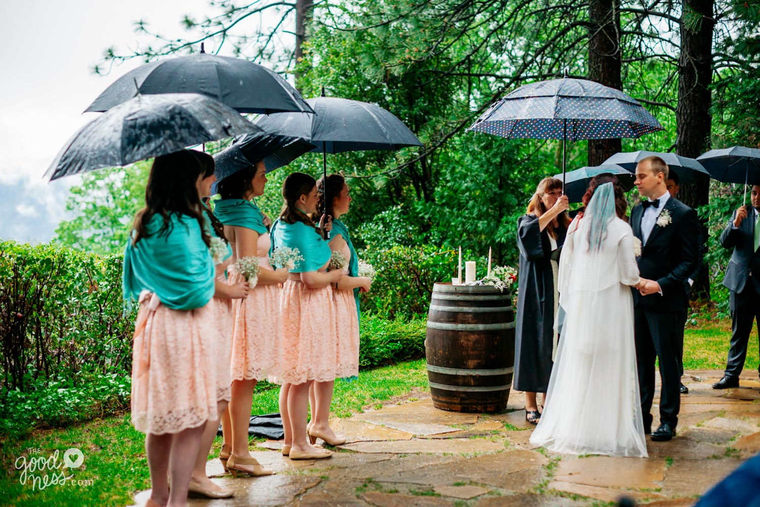 Minister and bridesmaids holding umbrellas during rainy wedding ceremony in Foresthill, California.