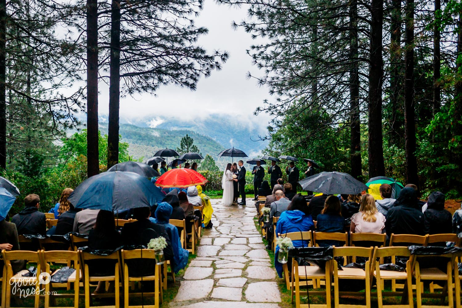 View of rain at Grand Sierra Pointe wedding ceremony site in Foresthill, California, with guests wearing rain slickers and holding umbrellas, and bridal party members also holding umbrellas