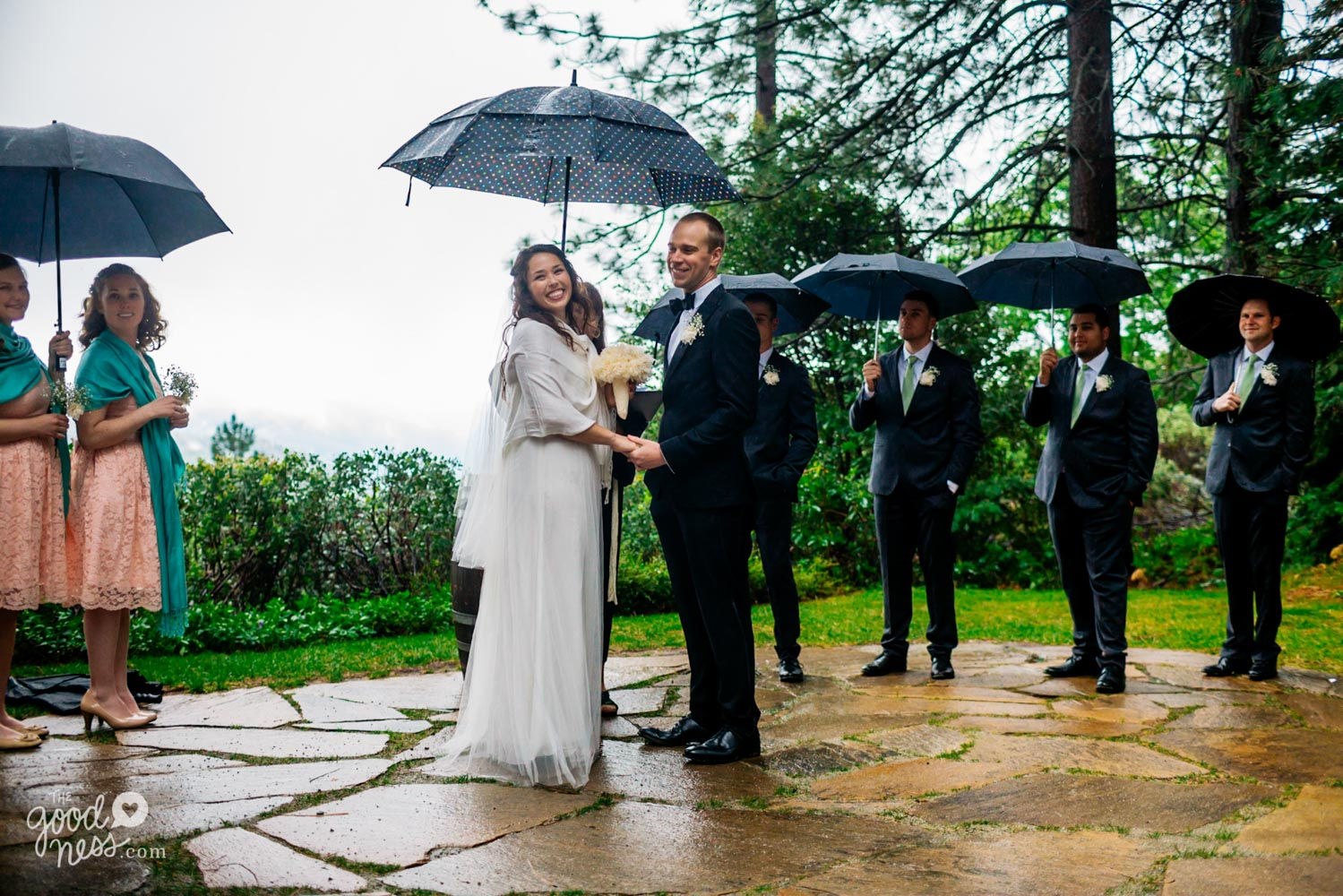 Smiling bride and groom, with wedding party in background holding umbrellas during rainy wedding ceremony in Foresthill, California.