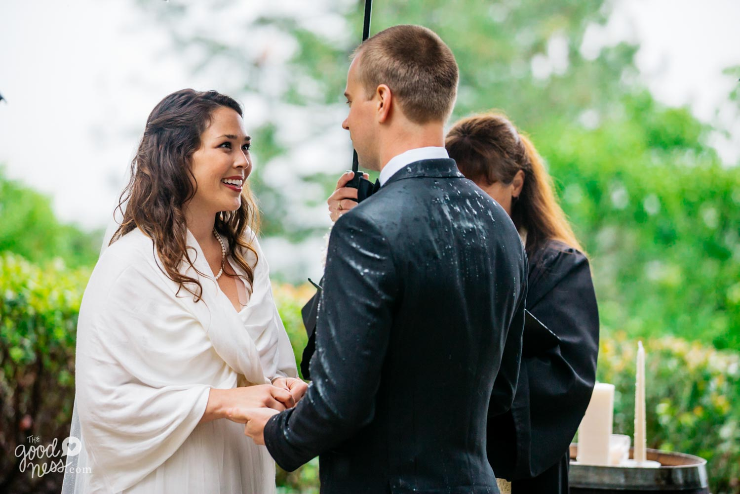 Bride smiling at groom, whose suit jacket is wet with rain, while officiant holds umbrella in background.