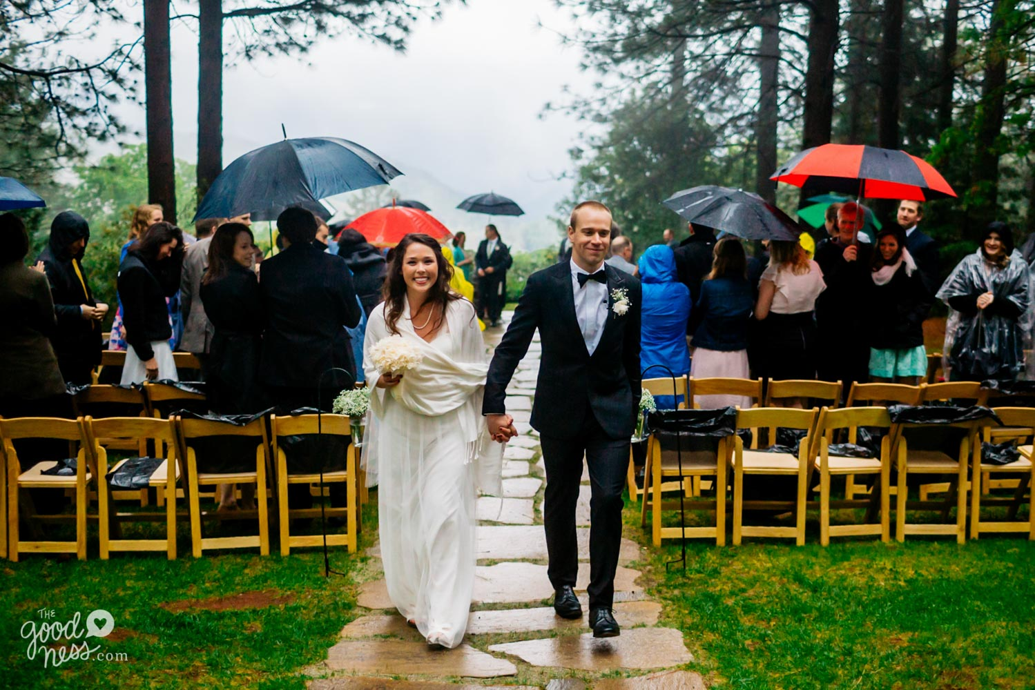 Smiling bride and groom walking up paved path while guests hold umbrellas and watch following rainy wedding ceremony at Foresthill, California.