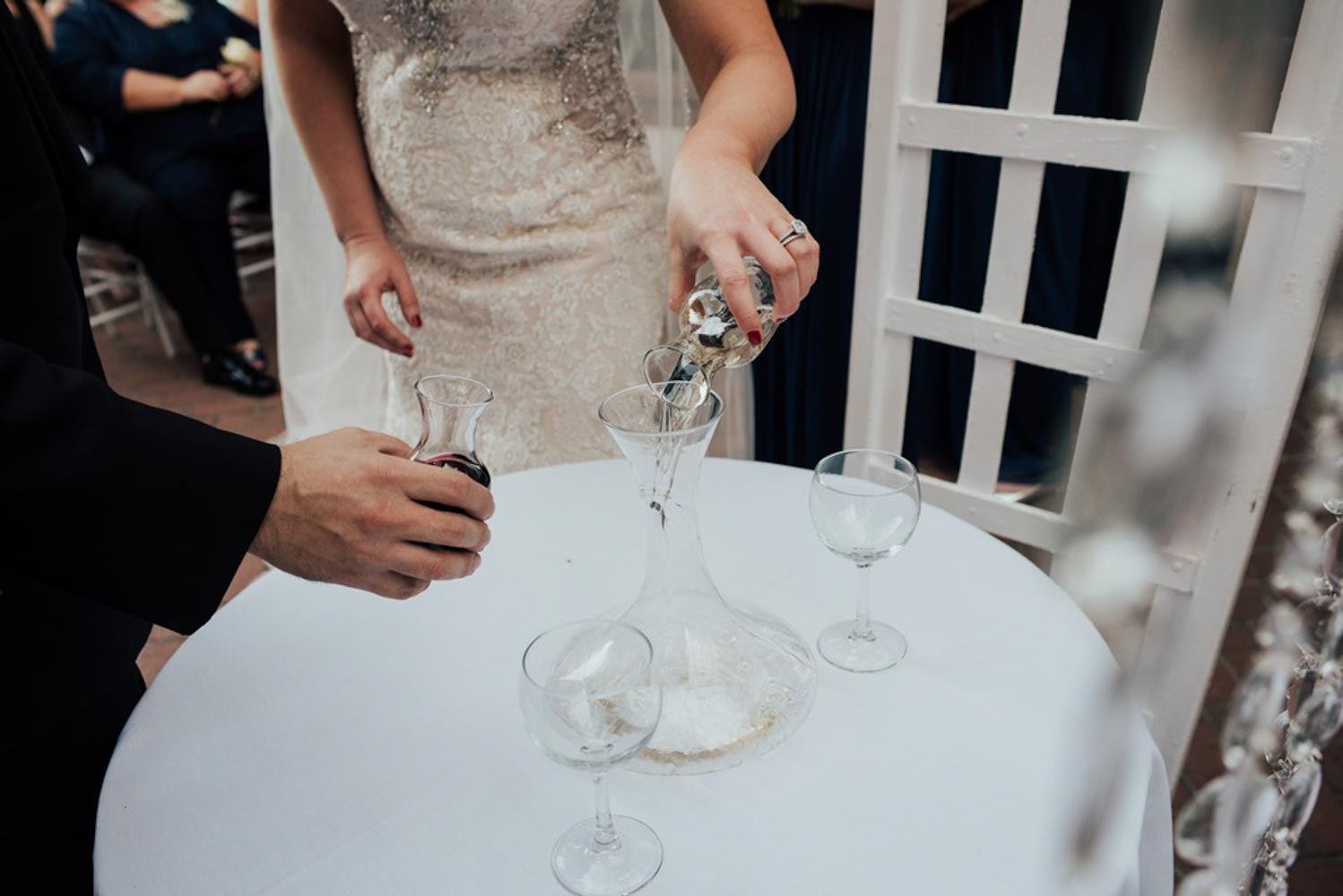 Photo of the hands of bride and groom pouring wine into larger Marriage Carafe