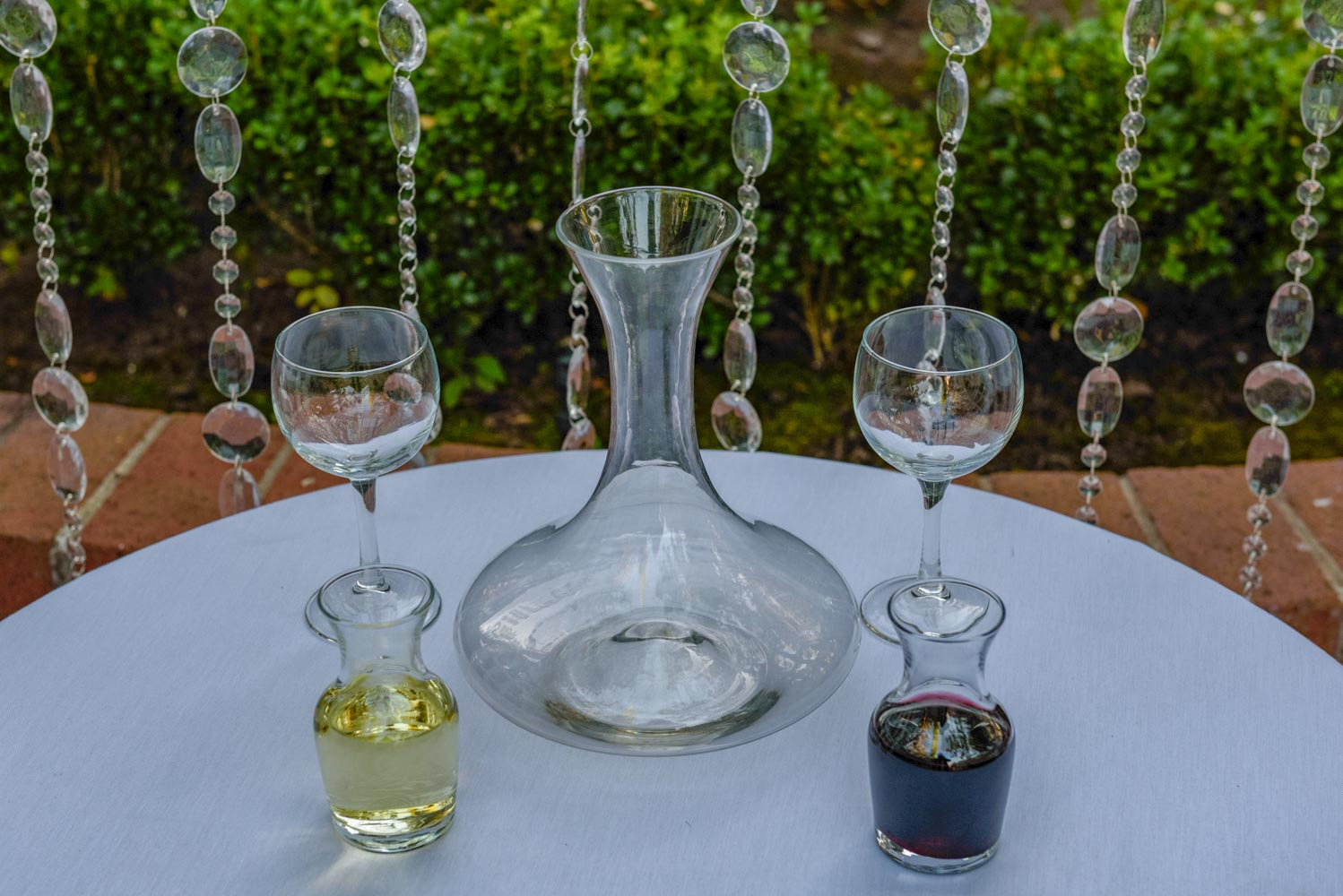 Two empty wine glasses, large empty carafe, and two small carafes with white and red wine, on table with strings of beaded crystals in garden background.