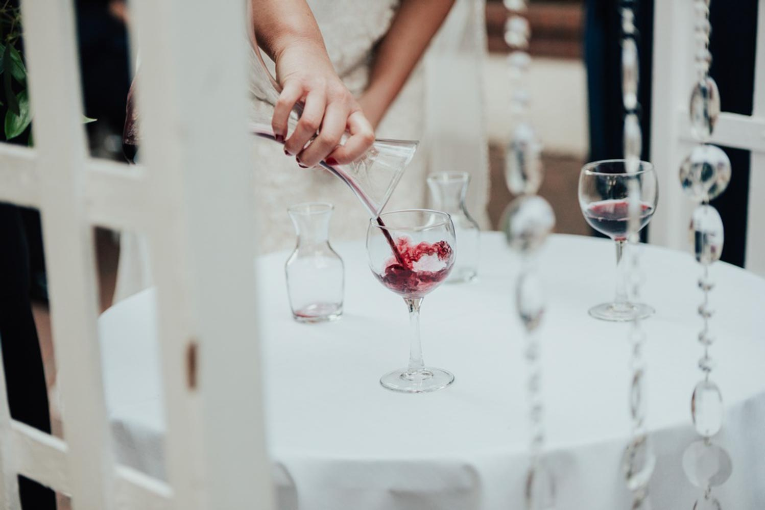 Groom pouring blended wine from the Marriage Carafe into a wine glass.