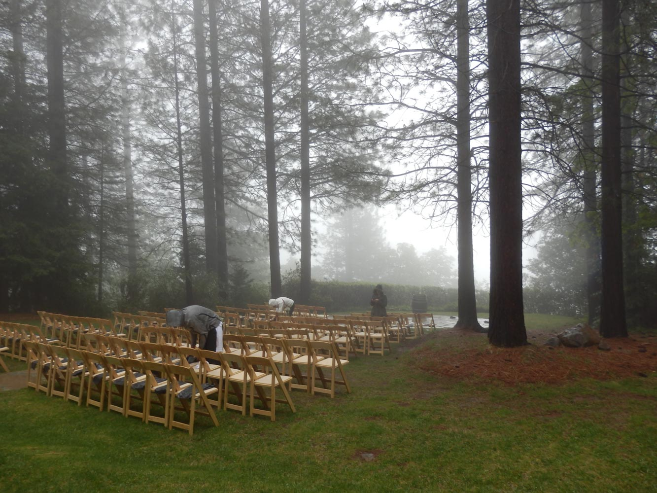 Staff in rain gear wiping down rows of wooden chairs at wedding ceremony site, with light rain falling.
