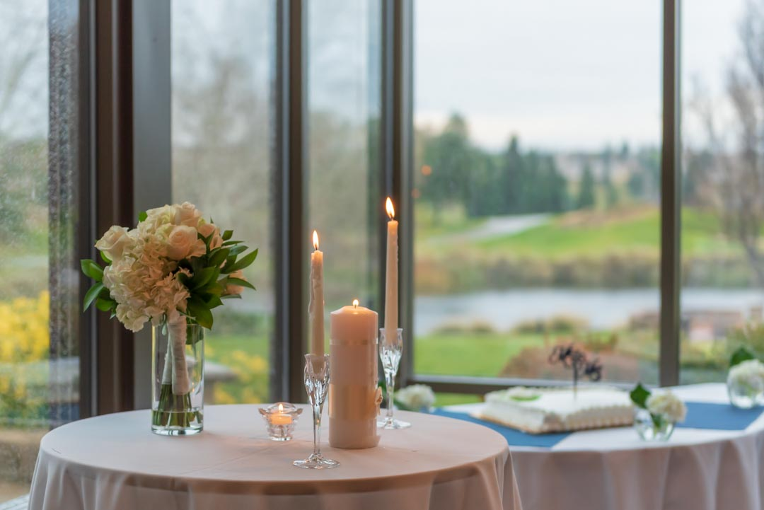 White linen-covered table holding bridal bouquet, lit unity candle and two tapers, with Orchard Creek Lodge landscape in background.