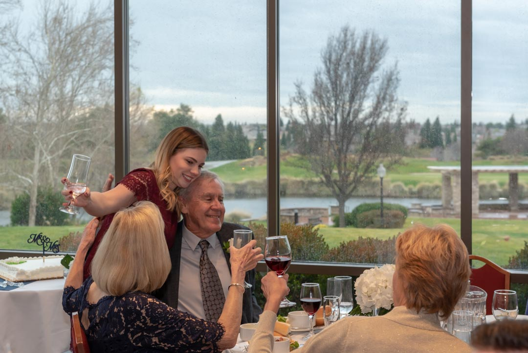 Young woman holding toasting glass and embracing older man during wedding reception at Orchard Creek Lodge.