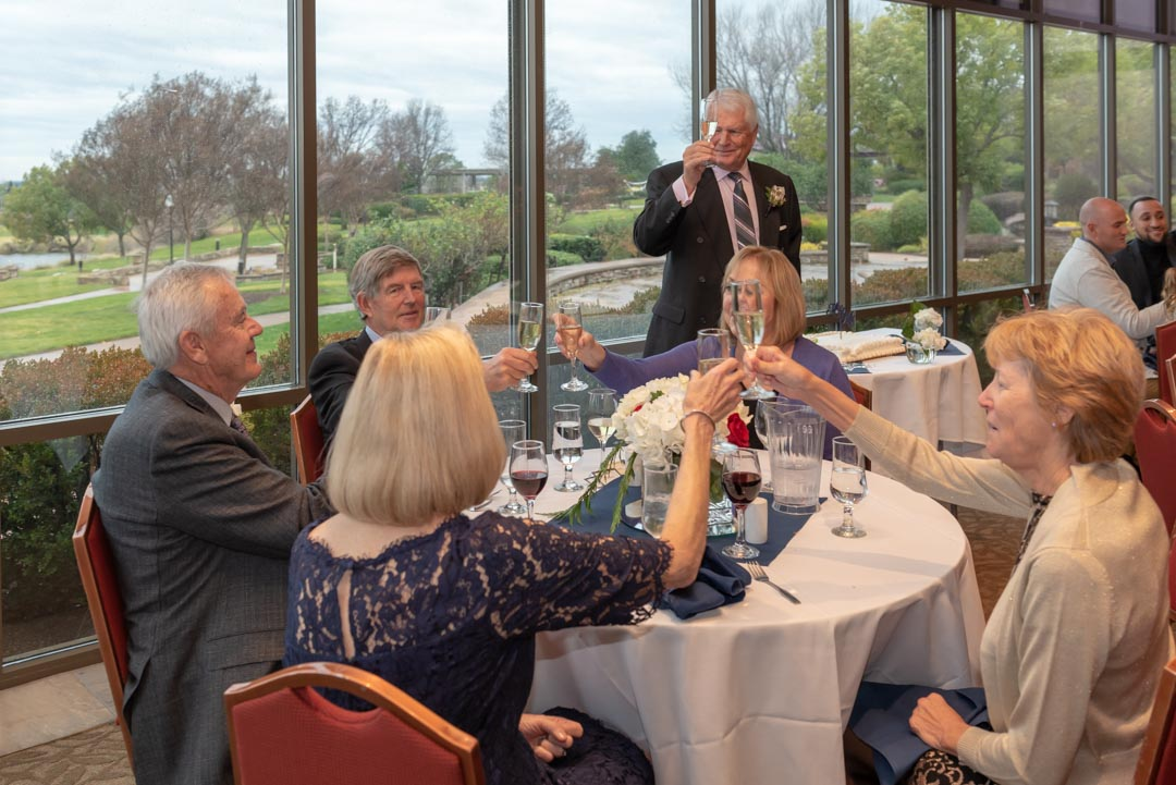 Adult man standing and holding up toasting glass, while seated bride, groom and wedding guests raise their glasses as well.