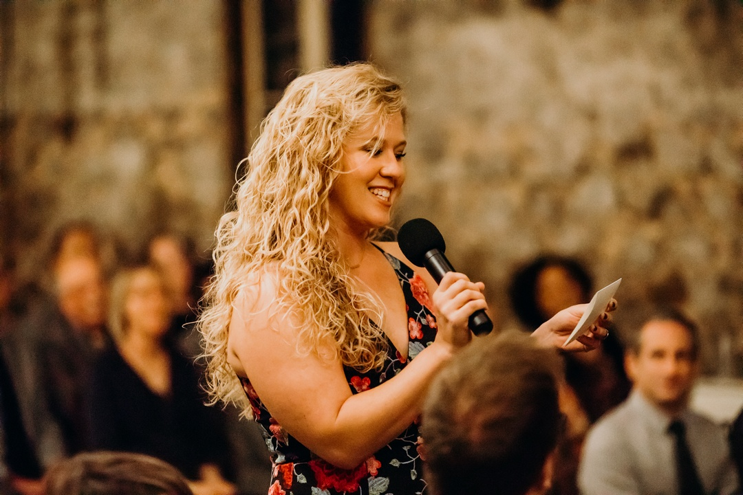 Smiling woman standing, holding microphone, and reading blessing during wedding ceremony at Miners Foundry, Nevada City, California.