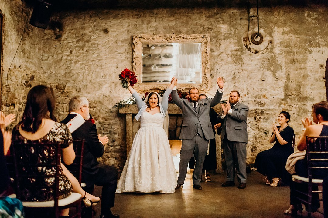 Bride and Groom raising arms in celebration at the concluding of their wedding ceremony at Miners Foundry, Nevada City, California.