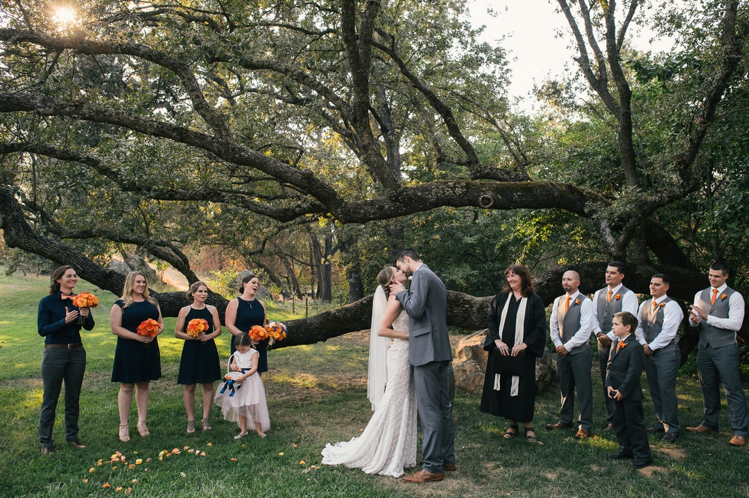 Wedding party and minister watching bride and groom kiss at end of wedding ceremony, held under giant oak tree at Gold Hill Gardens, Newcastle, California.