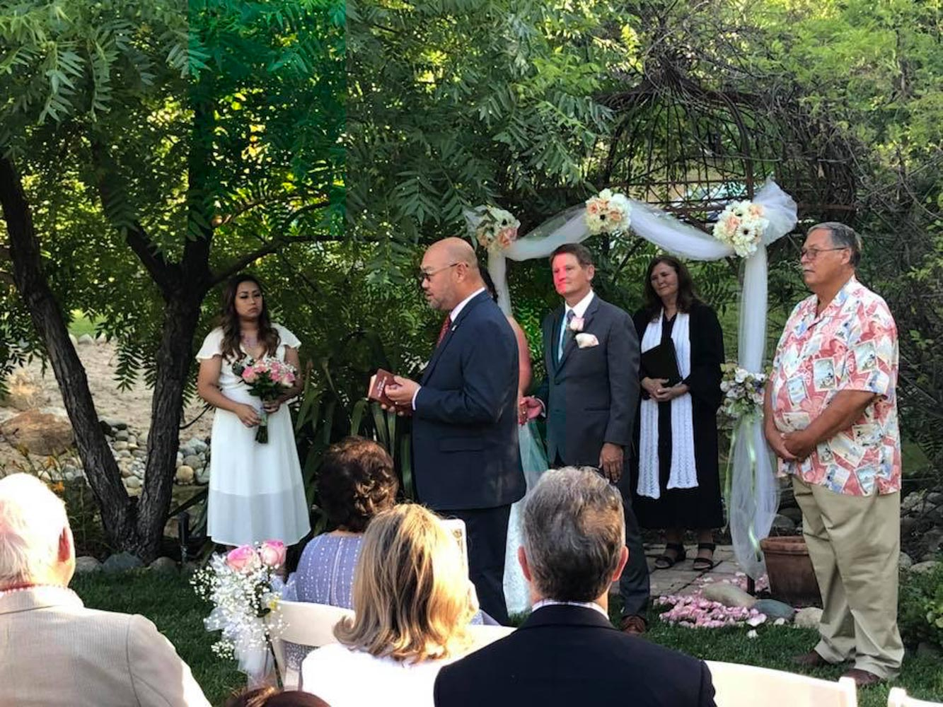 Minister, bride, groom and guests listening to man presenting reading during garden wedding ceremony.