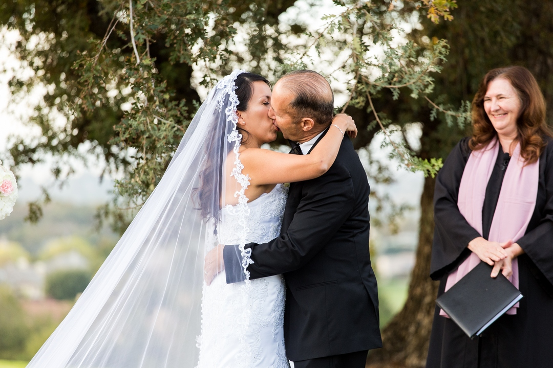 Photo, taken by Siegel's Portrait Design, of bride and groom kissing after being pronounced married, while minister smiles and applauds in the background.