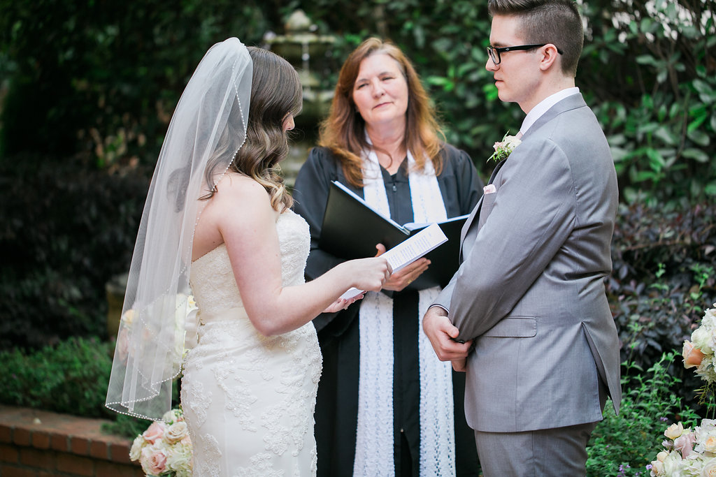 Bride reading vows to groom while officiant listens during garden wedding ceremony.