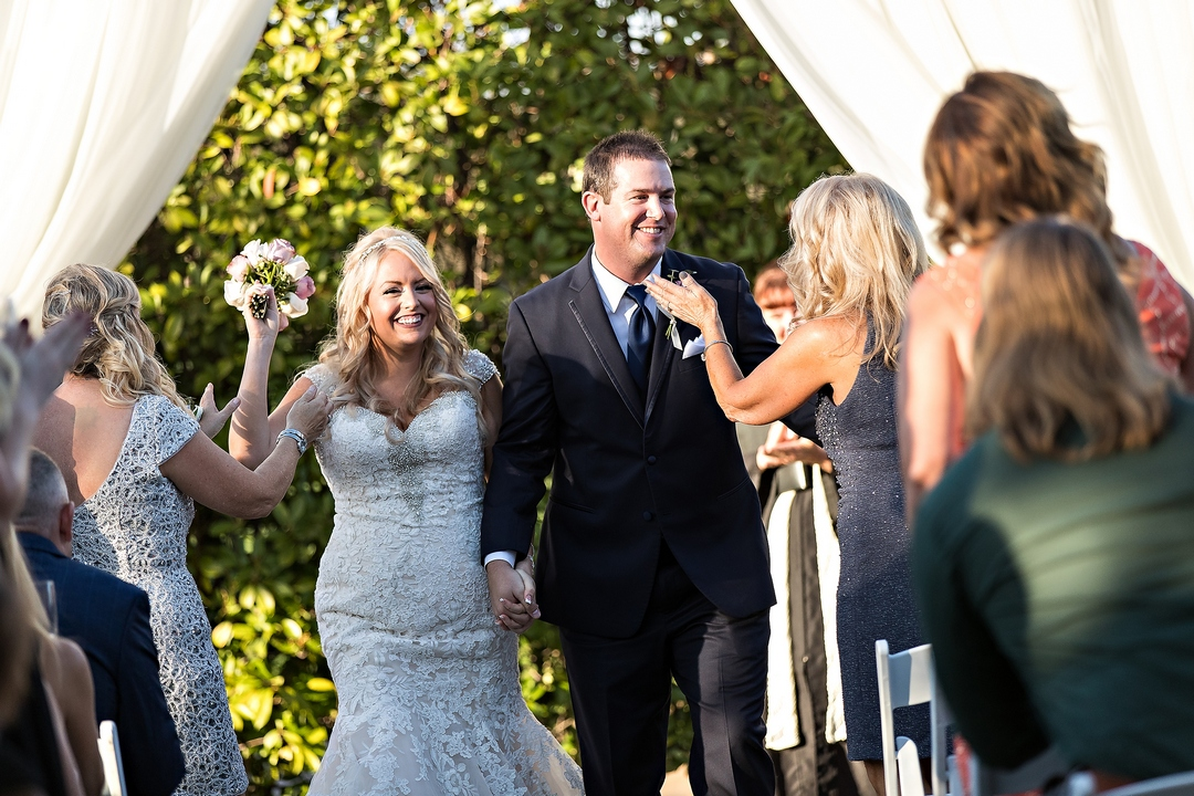 Photograph, taken by Siegel's Portrait Design, of smiling bride and groom walking down aisle, with guests applauding on both sides of the aisle following outdoor wedding ceremony.